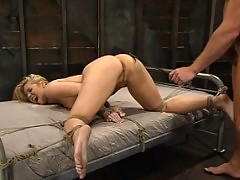 Hollie Stevens endures pain in bondage while fucked.
